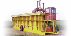 A modern module builder with cab for operator comfort and hydraulic drive system. A tractor provides PTO power to drive the hydraulic pump and drawbar power to move the builder. (Photo courtesy of KBH, Inc.)